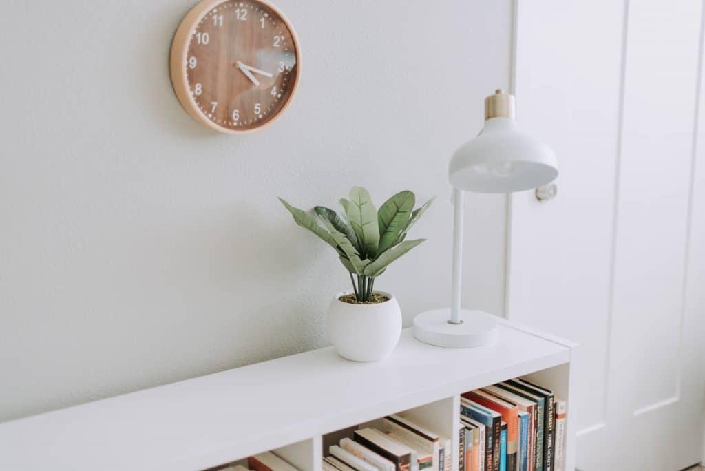 Une horloge au mur, au-dessus d'une bibliothèque
