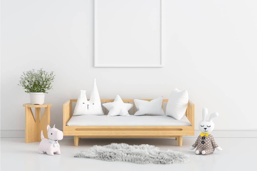Une chambre d'enfant épurée mais bien décorée avec des coussins et des peluches